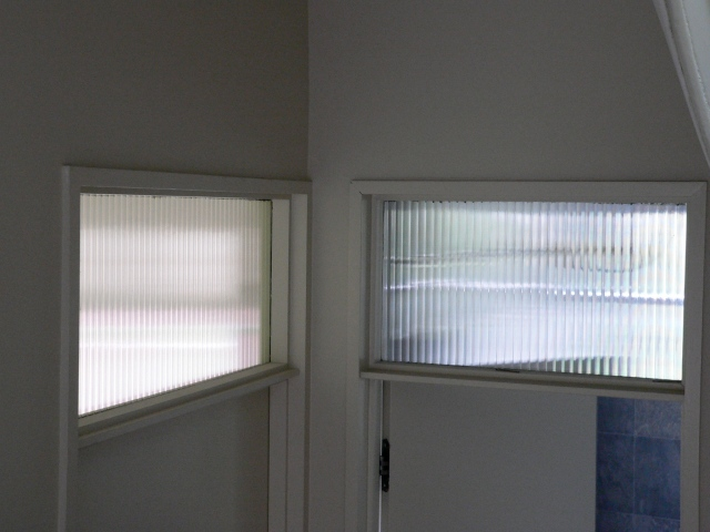 Ribbed glass transoms over doors let light into the upstairs hall